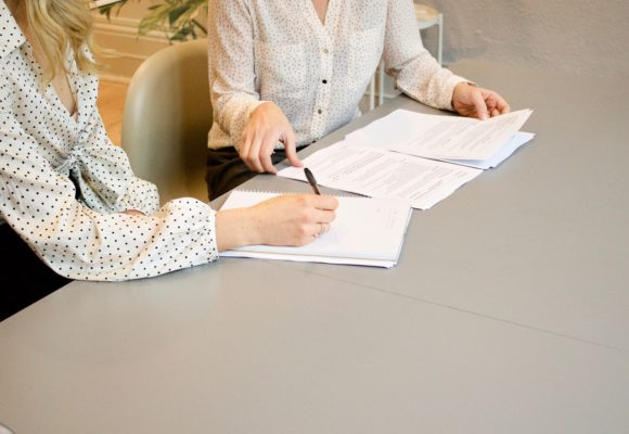 obrazek przedstawia ludzi podpisujących dokumenty rekrutacyjne